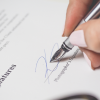 Person's hand signing a document
